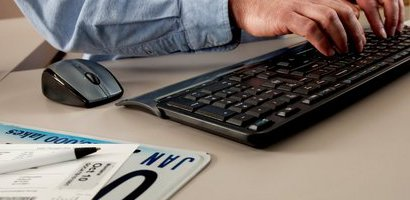 Hands on keyboard and license plate on desk